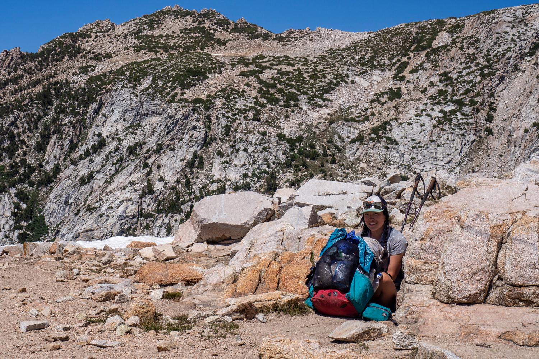 Holly versteckt sich auf dem Silver Pass hinter ihrem Rucksack, um sich vor dem Wind zu schützen